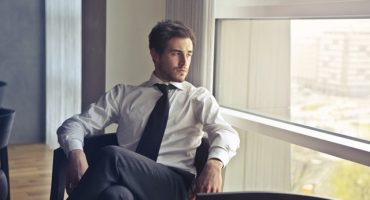 stock photo of a man in a tie sitting by a window
